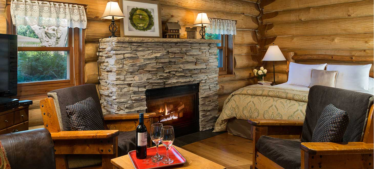 Fireplace, queen bed, lounge area inside Paul Bunyan Log Cabin at Justin Trails Resort in Sparta, Wisconsin
