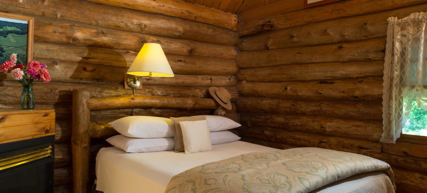 Romantic Log Cabin near La Crosse Wisconsin - Dog-Friendly log cabin Queen bed with log headboard inside Little House on the Prairie log cabin